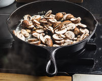 Sauteing sliced mushrooms in a skillet Stock Photos