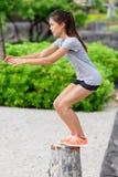 Sauter accroupi de saut de banc de femme de forme physique sur la plage Image libre de droits
