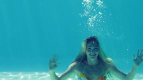 Sauter blond heureux dans la piscine et ondulation clips vidéos
