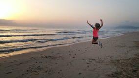 Sauter de fille heureux avec le lever de soleil Photos stock