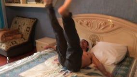Sauter en baisse d'homme sur l'essai de détente heureux de lit de dormir, temps de partie, vacances banque de vidéos