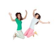 Sauter enthousiaste heureux de deux jeunes femmes Photographie stock libre de droits