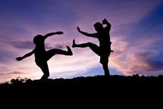 Sauter heureux de silhouette contre beau dans le coucher du soleil Liberté, e Image stock