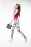 Sauter modèle de brune avec la jambe et tenir le sac de point de polka Photographie stock libre de droits
