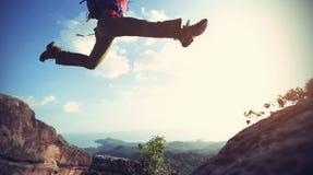 Sauter par-dessus le précipice entre deux montagnes rocheuses au coucher du soleil photos stock