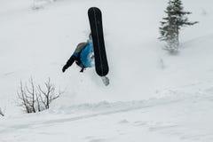 Sauter parasitaire de surfeur d'une rampe de neige sur un fond de forêt et de montagnes photos libres de droits
