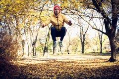 Sauter s'accroupit en nature Exercice de jeune homme Saison d'automne images libres de droits