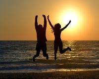 Sauter sur la plage pendant le lever de soleil Images libres de droits