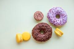 Sautez les butées toriques de style d'Art Color, les macarons et les sucreries de boulangerie sur le fond coloré lumineux Concept images stock