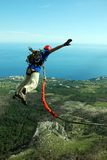 Sautez outre d'une falaise avec une corde Petite fille enthousiaste Image stock