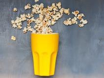 Sauts chaotiques de maïs éclaté de grande tasse jaune sur le fond bleu Photo libre de droits
