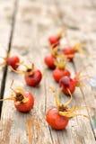 Sauvage rose de fruit s'est levé sur une vieille table en bois Images libres de droits