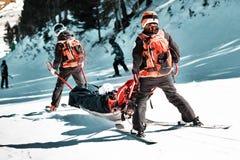 Sauveteurs à une station de sports d'hiver évacuer la victime de la pente image libre de droits