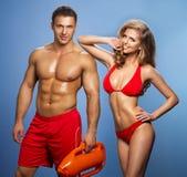 Sauveteurs sexy de couples de sourire de l'eau Image stock
