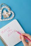 Sauvez l'écriture d'expression de date par la main de la femme dans le carnet Image libre de droits