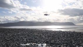 Sauvez l'hélicoptère volant au-dessus de la côte scénique au Pays de Galles du nord clips vidéos