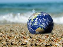 Sauvez la terre, la terre générée par ordinateur comme la planète sur une plage Vague écrasant à l'arrière-plan Concept approprié image libre de droits