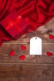 Sauvez le boîte-cadeau rouge enveloppé par prévision de téléchargement et la carte cadeaux sur la table en bois peut employer la  Image libre de droits