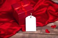 Sauvez le boîte-cadeau rouge enveloppé par prévision de téléchargement et la carte cadeaux sur la table en bois peut employer la  Photographie stock libre de droits