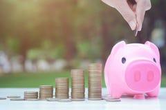 Sauvez le concept d'argent avec la main mettant la pièce de monnaie dans la pile de tirelire et de pièces de monnaie Images stock