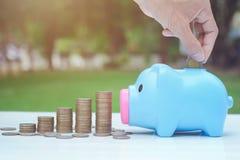 Sauvez le concept d'argent avec la main mettant la pièce de monnaie dans la pile de tirelire et de pièces de monnaie Photographie stock