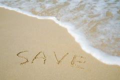 Sauvez le mot sur le sable de mer avec la mousse de mer Image stock