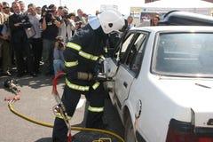 Sauvez le sapeur-pompier dans l'action pour enregistrer des personnes d'un accident de voiture Photos libres de droits