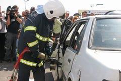 Sauvez le sapeur-pompier dans l'action pour enregistrer des personnes d'un accident de voiture Photo libre de droits