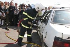 Sauvez le sapeur-pompier dans l'action pour enregistrer des personnes d'un accident de voiture Photos stock