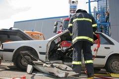Sauvez le sapeur-pompier dans l'action pour enregistrer des personnes d'un accident de voiture devant d'autres personnes à Sofia, Image stock