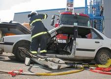 Sauvez le sapeur-pompier dans l'action pour enregistrer des personnes d'un accident de voiture devant d'autres personnes à Sofia, Photo libre de droits