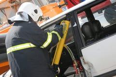 Sauvez le sapeur-pompier dans l'action pour enregistrer des personnes d'un accident de voiture devant d'autres personnes à Sofia, Photos stock