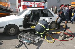 Sauvez le sapeur-pompier dans l'action pour enregistrer des personnes d'un accident de voiture devant d'autres personnes à Sofia, image libre de droits
