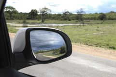 Savannah and blue sky on the rear mirror, Kruger National Park, South Africa. Savannah and blue sky on the rear mirror of the car, seen in Kruger National Park royalty free stock photo