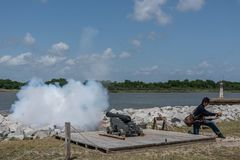 Savannah, Georgia - April 14, 2018: A reenactor fires the cannon daily at Old Fort Jackson. A Confederate Savannah River defense garrisoned by Union troops royalty free stock images