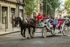 Horse carriage tour in Savannah. SAVANNAH, GEORGIA MARCH 1, 2018 People taking part in a guided horse carriage tour in the city of Savannah stock photo