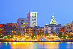 Savannah Georgia USA. Skyline of historic downtown at sunset with illuminated buildings and steam boats Royalty Free Stock Images