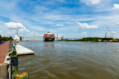 Savannah River. Savannah, GA USA - April 25, 2016: Large container ship cruising down the Savannah River towards the Talmadge Memorial Bridge Stock Photos