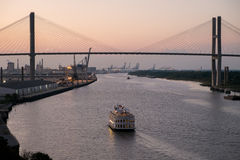 Savannah River at sunset. Savannah, GA, USA - October 13, 2014:Riverboat cruises at dusk on Savannah River below the Eugene Talmadge Memorial Bridge. Established Stock Photo
