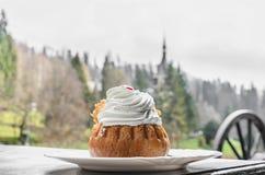 Savarin-Kuchen mit Sahne und Sirup, weiße Platte, Hintergrund im Freien stockfotografie