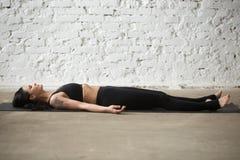 年轻Savasana姿势的,白色顶楼backgro信奉瑜伽者可爱的妇女 库存照片