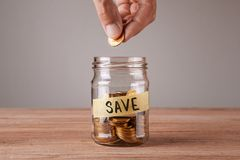 save Το βάζο γυαλιού με τα νομίσματα και μια επιγραφή σώζουν Το άτομο κρατά το νόμισμα στοκ εικόνες με δικαίωμα ελεύθερης χρήσης
