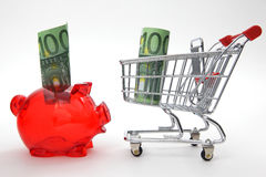 Save or buy?. Piggy bank with shopping cart on white background - save or buy royalty free stock image