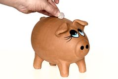 Save coin in a piggy. Picture of Save a coin in a piggy with a hand in a white background royalty free stock photos