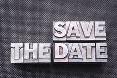 Save the date bm. Save the date phrase made from metallic letterpress blocks on black perforated surface Stock Images