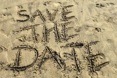 Save the date concept written on sand beach. On a sunny bright day royalty free stock images