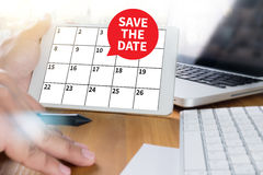 SAVE THE DATE message on hand holding to touch a phone, top view Royalty Free Stock Image