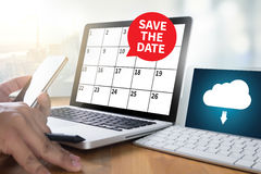 SAVE THE DATE message on hand holding to touch a phone, top view Stock Photos