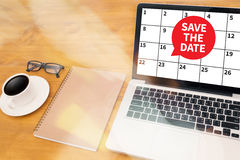 SAVE THE DATE message on hand holding to touch a phone, top view Stock Photo
