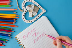 Save the date phrase writing by womans hand in notebook Stock Photos